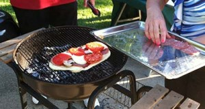 Adding toppings to grilled pizza